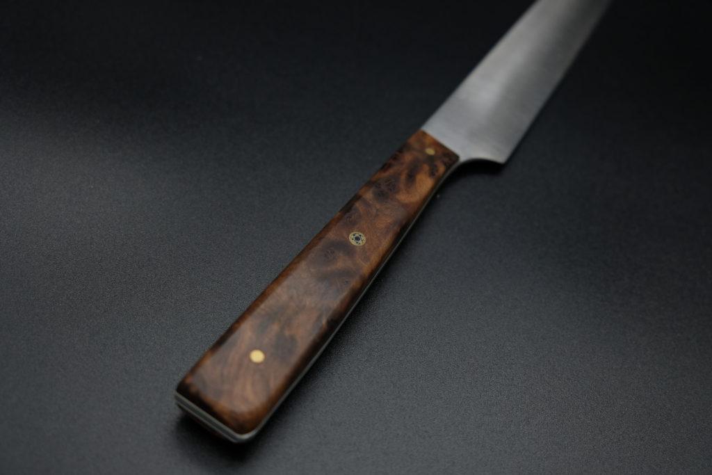 Yanagiba 24 cm, lama in acciaio Nitro B, manico in radica di Thuja, spaziatori in fibra vulcanizzata bianca e Mosaic Pin.